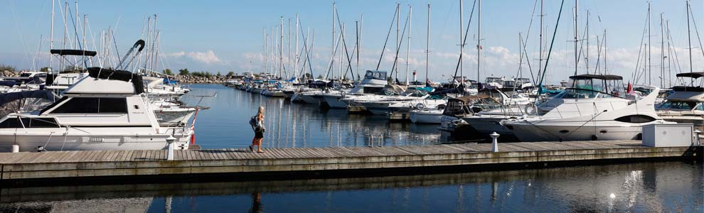 Oakville waterfront with boats docked and woman walking across a long dock