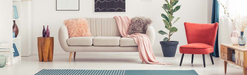White couch with pink blanket and furry pillows