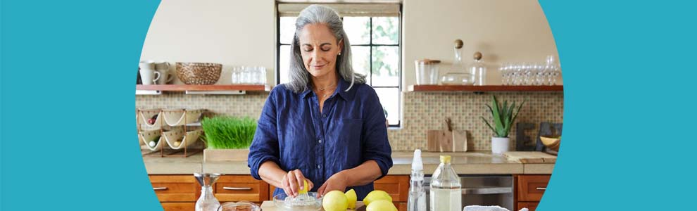 woman in kitchen slicing lemons for cleaning