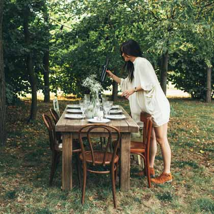 girl in park setting up an outdoor dinner table