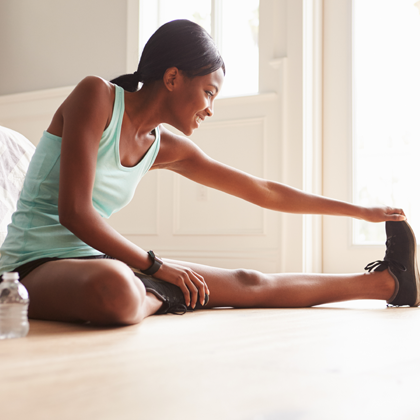Workout in small space - girl stretching on bedroom floor