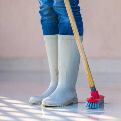 Winter tidy-up tips - girl sweeping in rubber boots