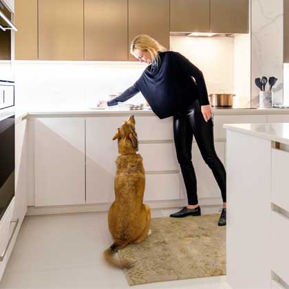 blonde girl giving dog a treat in Minto Yorkville apartment kitchen