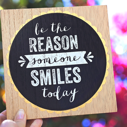 Random acts of kindness - person holding sign that says be the reason someone smiles today
