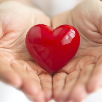 Giving back to your community - person holding red, fake heart in hands