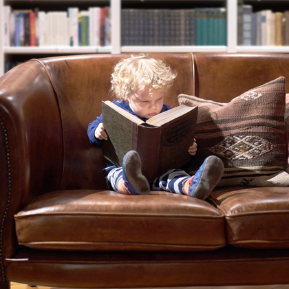 toddler reading large book on brown leather couch