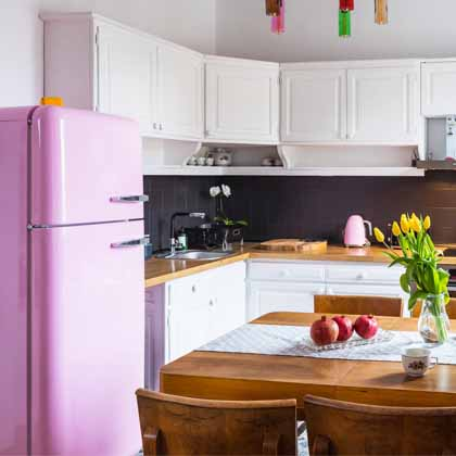kitchen with pink smeg fridge and yellow tulips