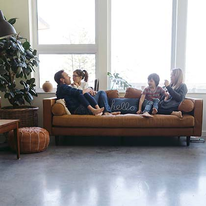 family of four on brown couch in comfortable living room