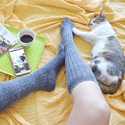 person wearing grey socks sitting on a yellow blanket with a cat, coffee, magazine and smart phone