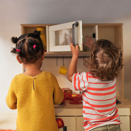 Two little kids playing in a miniature kitchen