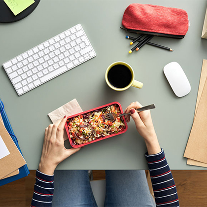 Woman eating vegan food at a desk