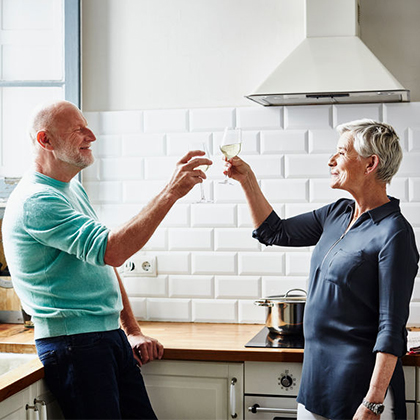 two mature adults toasting in kitchen