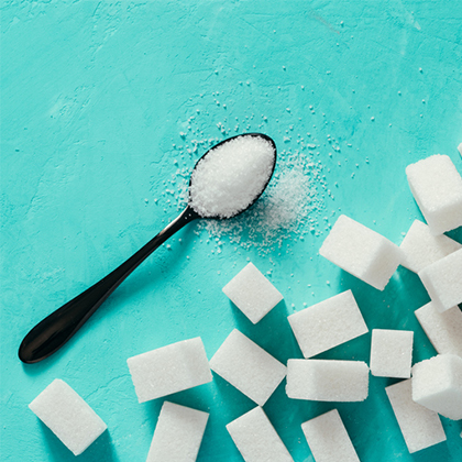 White sugar in a spoon next to numerous sugar cubes