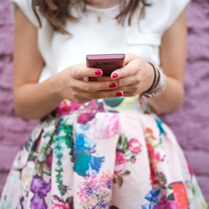 close-up of woman's hands holding a smartphone standing in front of purple brick wall
