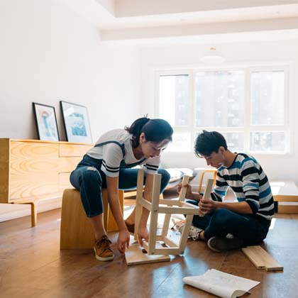 two young adults sitting on floor of empty apartment building stool