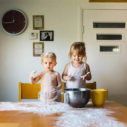 two children making a mess in the kitchen with flour