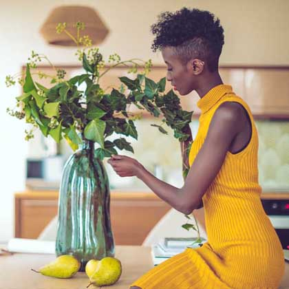 woman in yellow rearranging plants