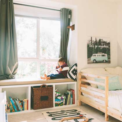 litte boy sitting in organized bedroom