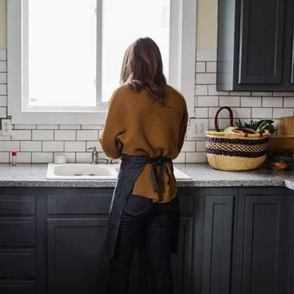 girl in black kitchen with reusable shopping bag