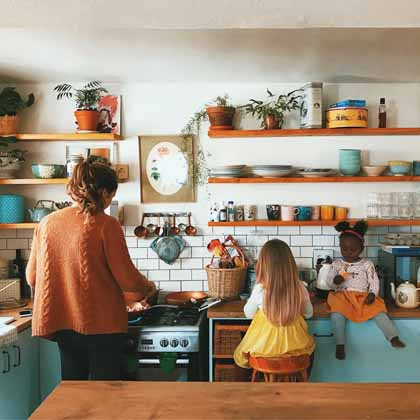 mom and two daughters cooking in an open shelf kitchen