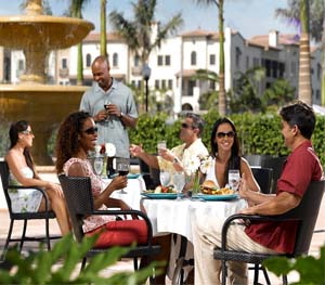 Friends enjoying lunch outdoors. Artesia homes in Sunrise, Florida have many amenities including terraces, spas and pools.