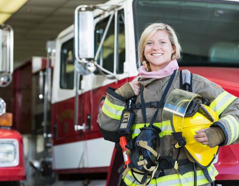 Female Firefighter standing outside her truck